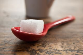 A sugar cube rests on a large spoon
