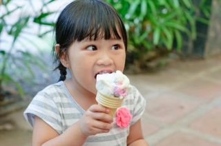 asian girl eating an ice cream cone.