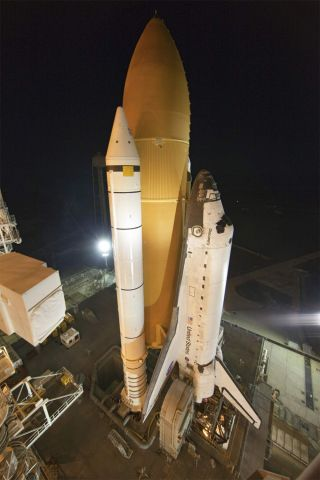 Space shuttle Discovery, secured to a crawler-transporter, slowly moves away from Launch Pad 39A at NASA's Kennedy Space Center in Florida, on its way to the Vehicle Assembly Building for repairs to its external fuel tank.