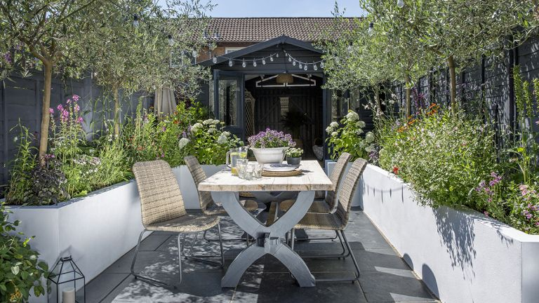 An outdoor dining table in a small garden