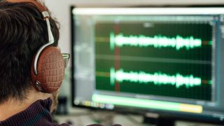 Close-up of a man's head wearing headphones in a recording studio