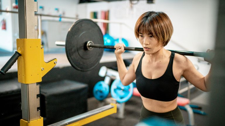 Woman exercising by doing squats in the gym
