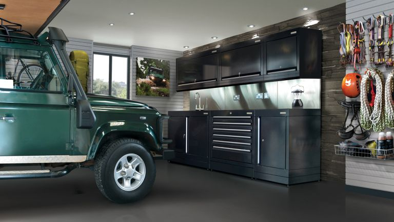 a landrover in a garage fitted with garage storage cabinets and hiking gear