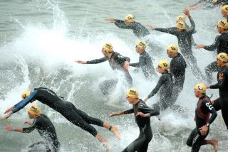 Triathletes at the start of a race, entering the water.