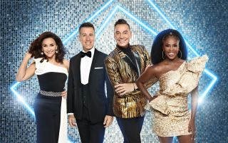 A group shot of Strictly judges Shirley Ballas, Anton Du Beke, Craig Revel Horwood and Motsi Mabuse in front of a silver glitter backdrop with light blue neon lights