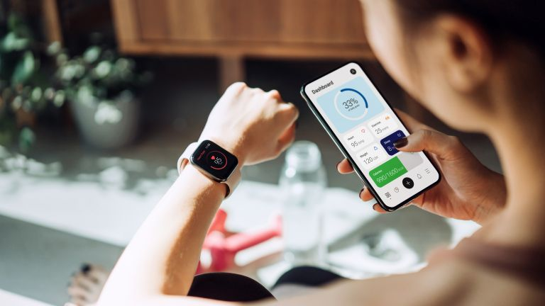 woman looking at one of the best workout apps with fitness tracker