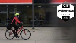 A woman cycles through a city street on a hybrid bike