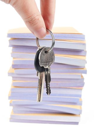 Stock photo of keys dangled in front of a stack of papers.