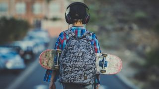 Child with a skateboard attached to his bag listens to music through a pair of headphones