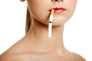 A cigarette, nearly broken in half, dangles from a woman's mouth.