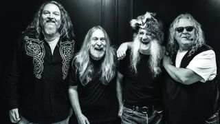 A black and white picture of The Kentucky Headhunters standing in a line and smiling.