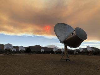 A view of the Allen Telescope Array shows antennas under a smoke-filled sky and a red-tinged sun on Sept. 7, 2021.