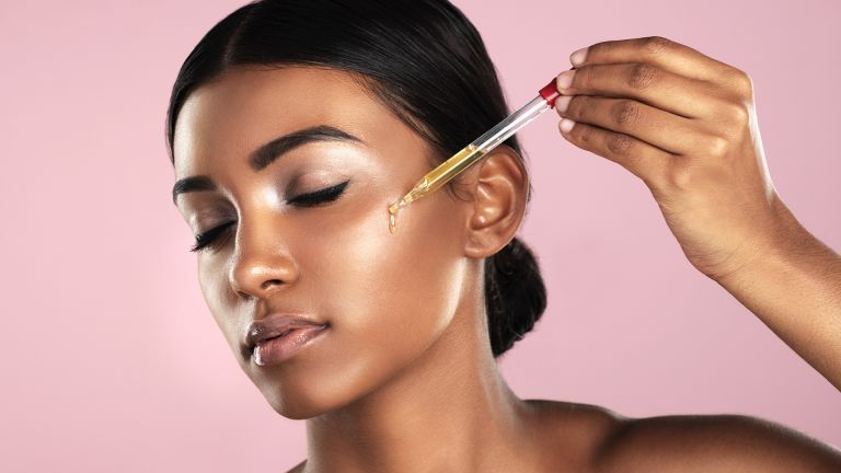 Studio shot of a beautiful young woman applying essential oil to her face with a dropper posing against a pink background