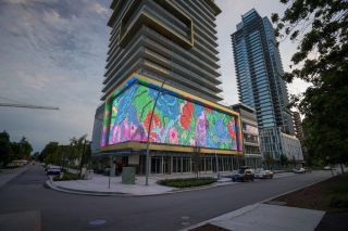 Outdoor LED mesh display transforms building into North America's largest digital art canvas with Planar displays.