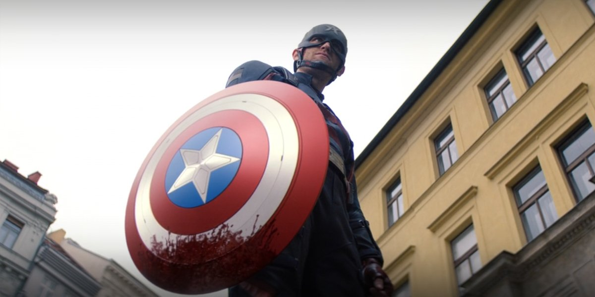 Wyatt Rogers as John Walker Captain America holding bloody shield in The Falcon And The Winter Soldier
