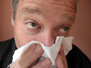 Man suffering from flu symptoms, new study reveals flu viruses circulate around the planet causing epidemics.