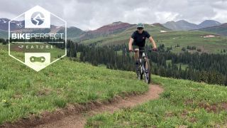Ryan Simonovich riding a bike on singletrack in Colorado, with trees and mountains in the background