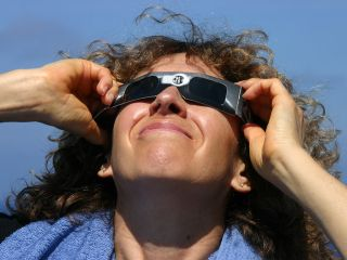 Woman looks upward with eclipse glasses on