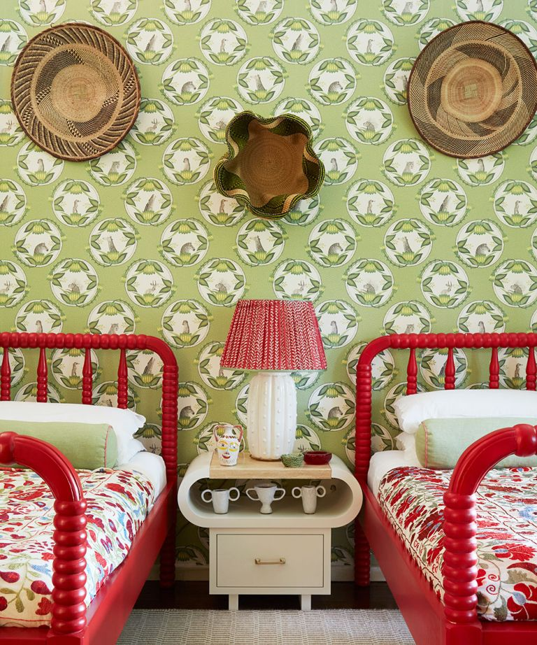 bedroom with twin beds, painted red against green pattern wallpaper