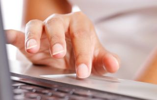 Stock image of person using laptop touchpad