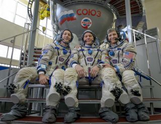 Astronauts Thomas Pesquet of ESA (European Space Agency), Oleg Novitskiy of the Russian space agency Roscosmos, and Peggy Whitson of NASA pose for a group photo at the Gagarin Cosmonaut Training Center in Star City, Russia during qualification exams for t