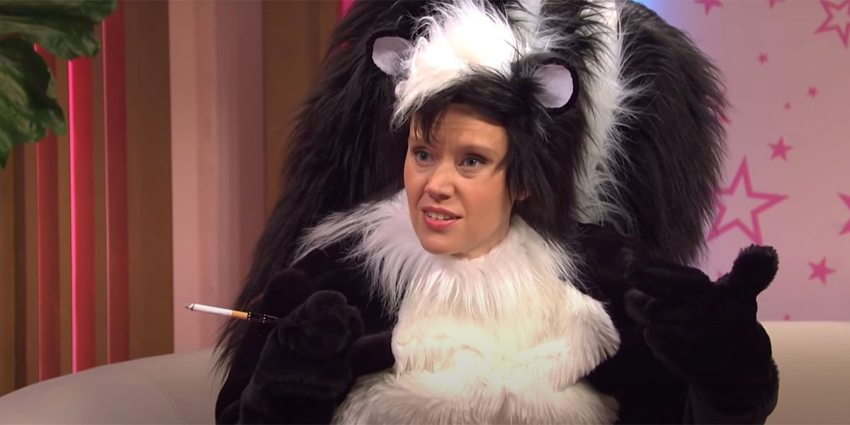 Kate McKinnon dressed as skunk Pepe Le Pew with her face exposed, smoking a cigarette and looking amused.