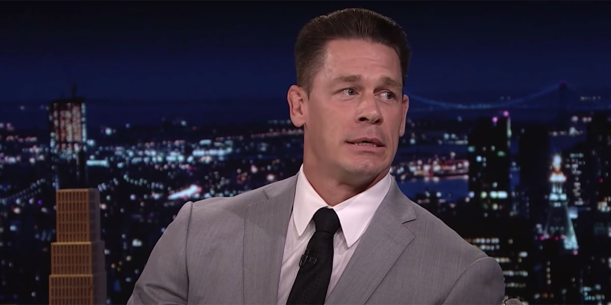 John Cena in a grey suit with a white shirt and black tie sitting for an interview on The Tonight Show.