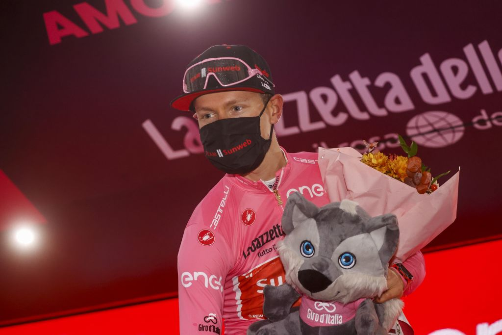Team Sunweb rider Netherlands Wilco Kelderman wearing the overall leaders pink jersey celebrates on the podium after the 19th stage of the Giro dItalia 2020 cycling race a 258kilometer route between Morbegno and Asti on October 23 2020 Heavy rain has interrupted on October 23 2020 the 19th stage of the Giro dItalia following protests by the riders in the face of difficult weather conditions Todays stage was planned to be a flat 258km ride between Morbegno and Asti but was cut back 100km after riders revolted when faced with pelting rain in the northern region of Lombardy Photo by Luca Bettini AFP Photo by LUCA BETTINIAFP via Getty Images