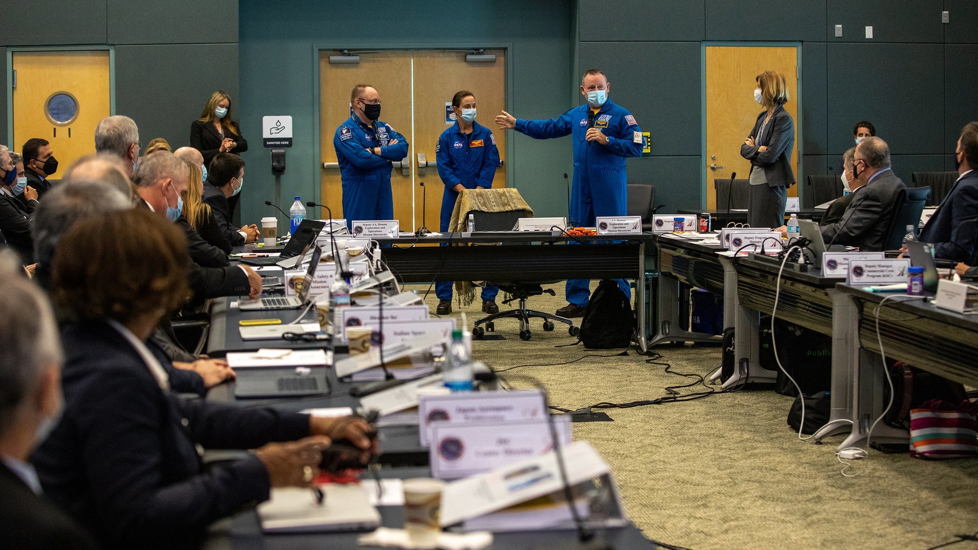 """Come parte di una revisione della prontezza di volo per l'Orbital Flight Test-2 (OFT-2) di Boeing, gli astronauti della NASA per testare il Boeing Crew Flight Test (CFT), il comandante Barry """"Butch"""" Willmore, il pilota Nicole Mann e il comandante delle operazioni congiunte E. Michael """"Mike"""" Fincke si rivolge ai manager della NASA e della Boeing presso l'Operations Support Building 2 presso il Kennedy Space Center della NASA in Florida, il 22 luglio 2021."""