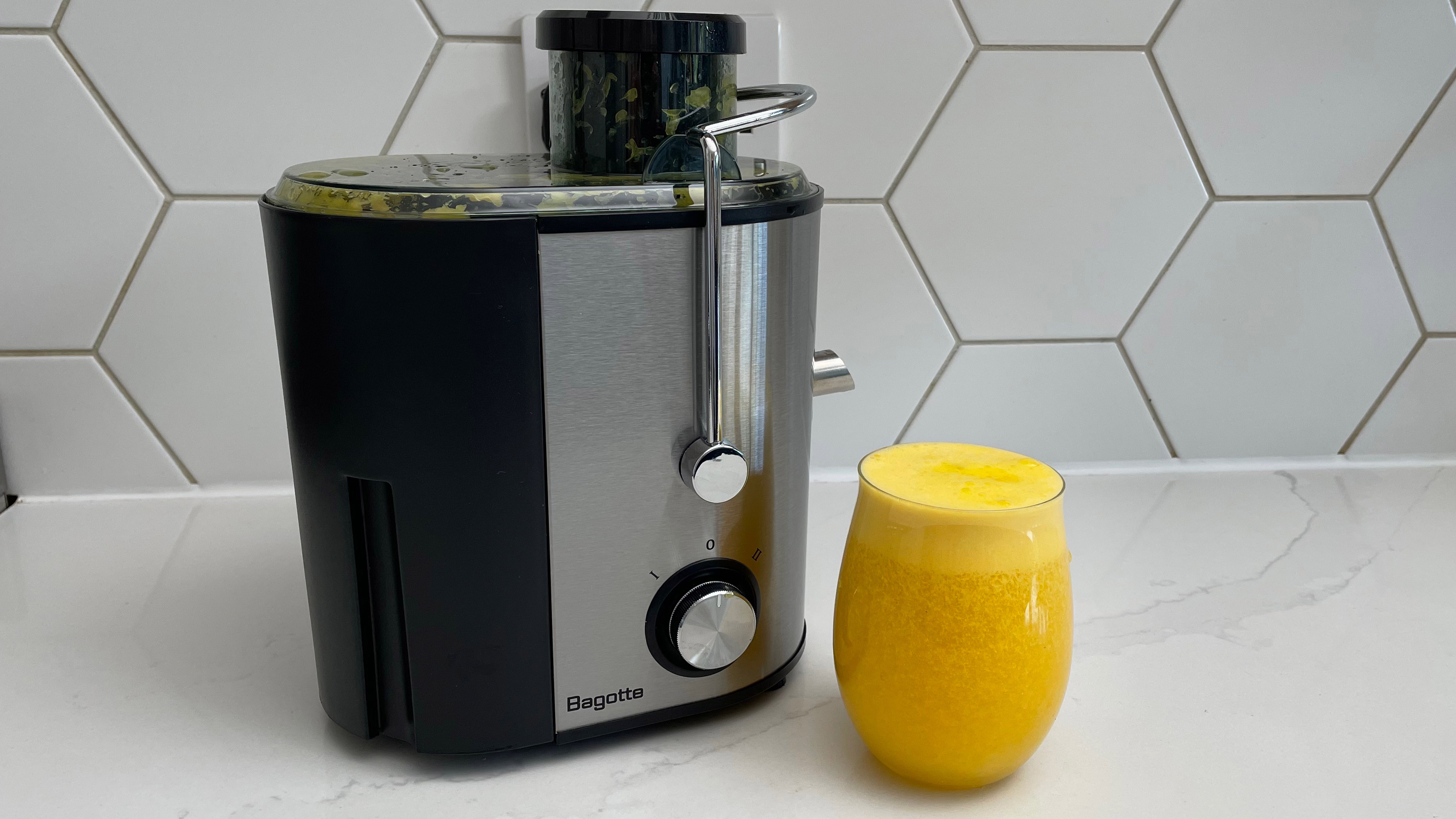 The Bagotte DB-001 juicer on a kitchen countertop with a glass of juice prepeared in the appliance
