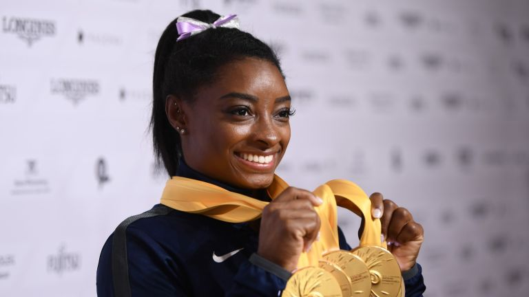 Simone Biles of USA poses with her Medal haul after the Apparatus Finals on Day 10 of the FIG Artistic Gymnastics World Championships at Hanns Martin Schleyer Hall on October 13, 2019 in Stuttgart, Germany.