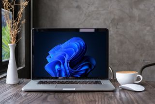 Apple Macbook pro computer with dried flower vase and latte art coffee on wooden table with Windows 11 wallpaper