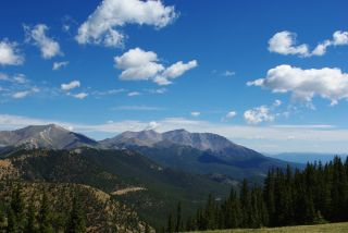 Clouds hover over the Rocky mountains, as seen from a distance.