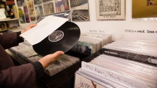 A picture of a man browsing the vinyl in a record store