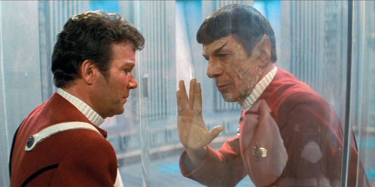 William Shatner as Captain Kirk looking through the glass at a dying Spock holding up live long and prosper hand sign in Star Trek: Wrath of Khan