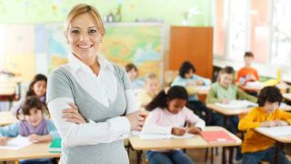 Smiling teacher stands in front of kids working at desks in classroom