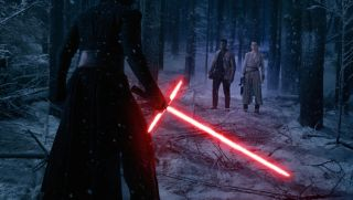 Kylo Ren facing Finn and Rey with lightsaber drawn.