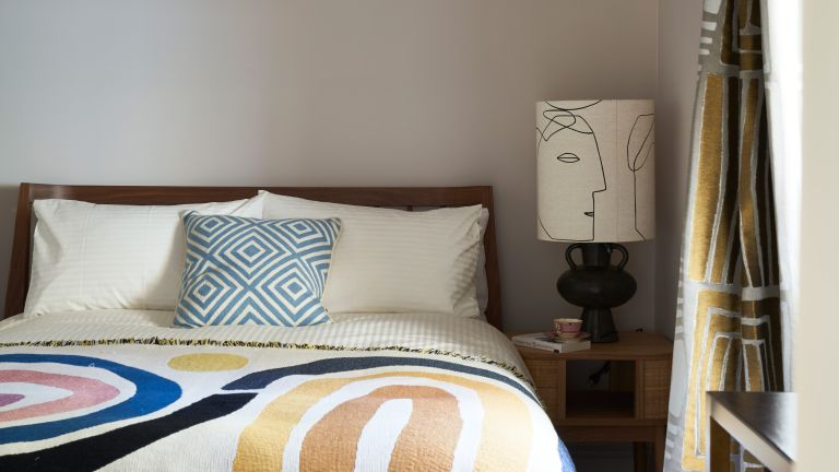 Cream guest bedroom with colorful throw and bedside lamp with modern print