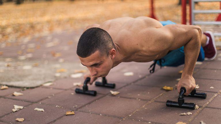 Man using push up handles, part of a home gym setup