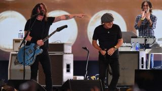 """Brian Johnson (C) from ACDC laughs with Dave Grohl (L) of US rock band the Foo Fighters as they perform onstage during the taping of the """"Vax Live"""" fundraising concert at SoFi Stadium in Inglewood, California, on May 2, 2021"""