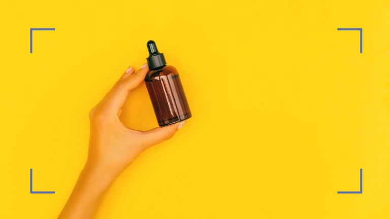 Bottle of argan oil being held by a hand against a yellow background. Blue illustrative corner details in each corner