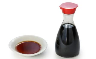 a bottle of soy sauce with a dipping dish