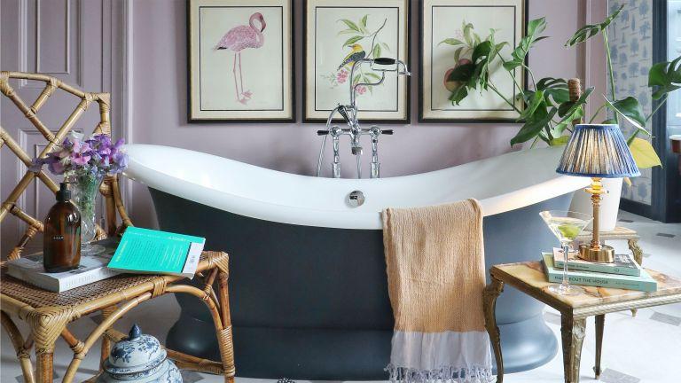 A pink bathroom idea with navy freestanding bath, framed bird wall art, a rattan chair, lampshade
