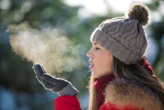 A woman watches her exhaled breath turn to steam in cold weather.