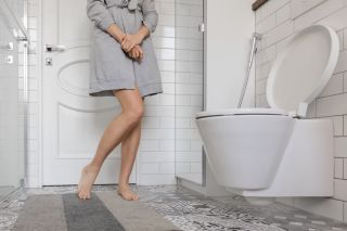 A woman with prostate problems stands next to a toilet.