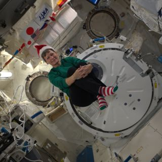 NASA astronaut Peggy Whitson dons a Santa hat and Christmas socks in weightlessness to celebrate the holidays on the International Space Station on Dec. 22, 2016.