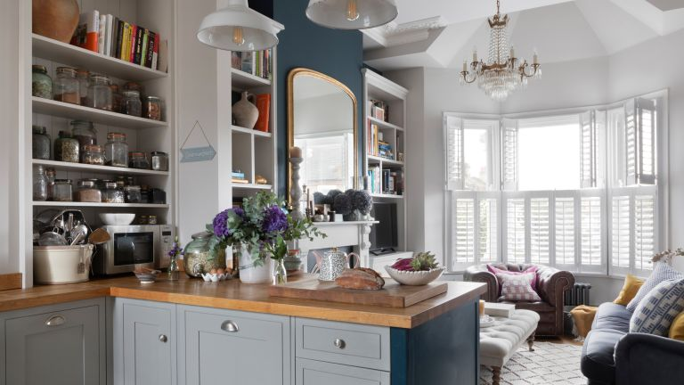 Pippa Jones house: shot from kitchen into living room with big bay window, white shutters, and dark blue feature wall with oversized mirror over white fireplace