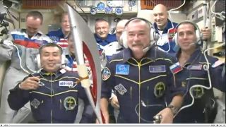Russian cosmonaut Mikhail Tyurin holds the Olympic torch for the 2014 Olympic Games during a press conference on Nov. 7, 2013 between his Expedition 37/38 crew and Russia's Mission Control on Earth.