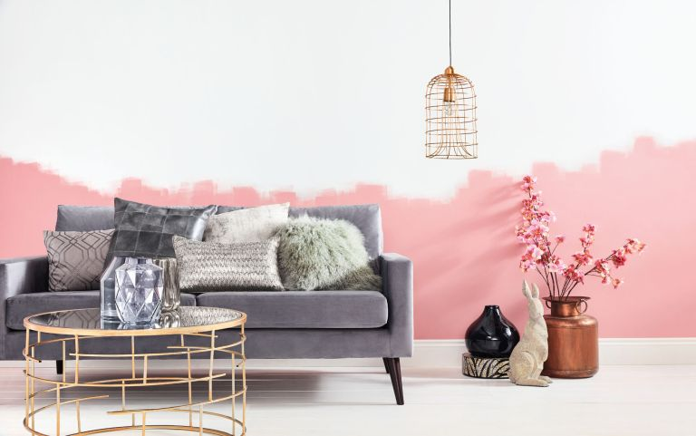A grey sofa with assorted scatter cushions against a pink and white wall
