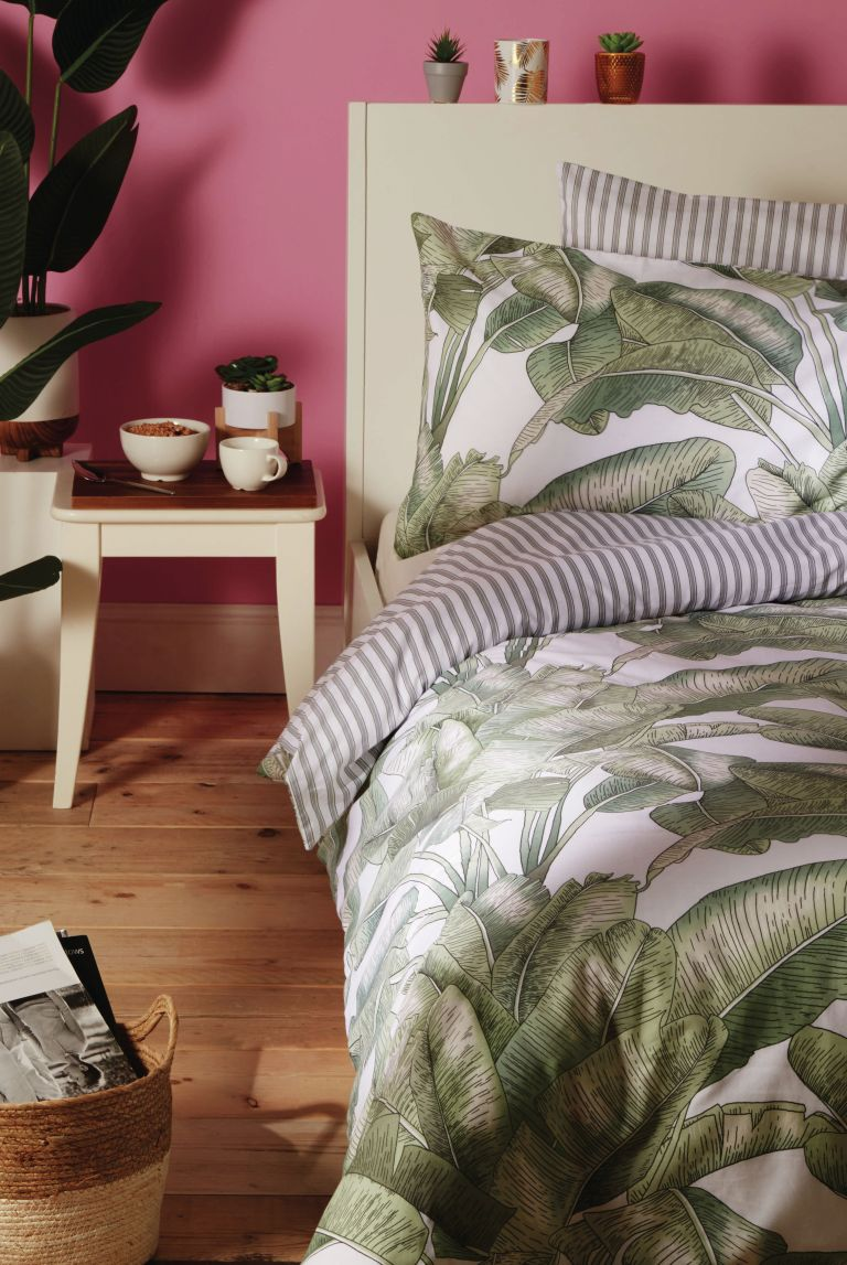 Primark home bedroom with pink walls, botanical leaf bed linen and a wooden side table with plant pots